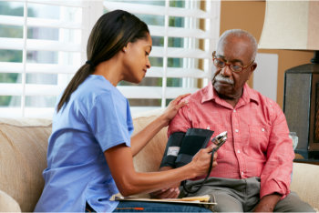 nurse checking the health of a senior man at home