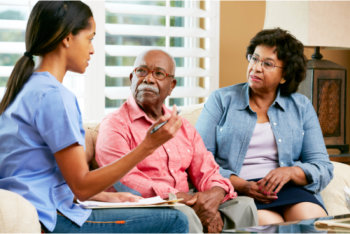 healthcare staff talking to an elderly couple