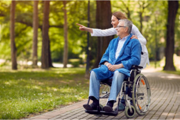 caregiver assists the senior man outside the house
